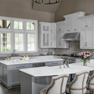 На фото: огромная п-образная кухня-гостиная с раковиной в стиле кантри, фасадами с утопленной филенкой, белыми фасадами, столешницей из кварцевого агломерата, серым фартуком, фартуком из мрамора, техникой из нержавеющей стали, полом из керамогранита, двумя и более островами, коричневым полом, белой столешницей и сводчатым потолком
