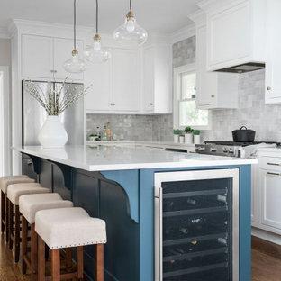 アトランタの広いトランジショナルスタイルのおしゃれなキッチン (アンダーカウンターシンク、フラットパネル扉のキャビネット、白いキャビネット、クオーツストーンカウンター、グレーのキッチンパネル、セラミックタイルのキッチンパネル、シルバーの調理設備、無垢フローリング、茶色い床、白いキッチンカウンター) の写真