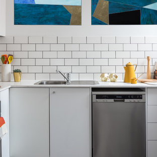Photo of a contemporary l-shaped kitchen in Sydney with a drop-in sink, flat-panel cabinets, white cabinets, white splashback, subway tile splashback, stainless steel appliances and no island.
