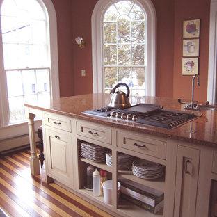 Immagine di una cucina vittoriana di medie dimensioni con ante con bugna sagomata, ante con finitura invecchiata e isola