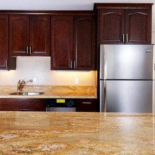 Immagine di una piccola cucina parallela tradizionale con lavello sottopiano, ante con bugna sagomata, ante in legno bruno, top in granito, elettrodomestici in acciaio inossidabile, nessuna isola e top arancione