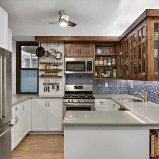 Klassische Küche in U-Form mit Unterbauwaschbecken, Glasfronten, hellbraunen Holzschränken, Küchenrückwand in Blau, Küchengeräten aus Edelstahl, hellem Holzboden, Halbinsel und braunem Boden in New York