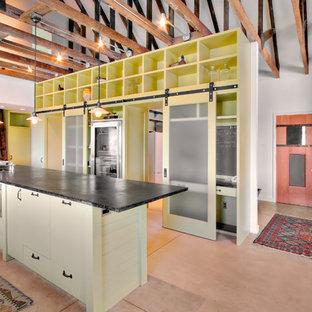 シアトルのインダストリアルスタイルのおしゃれなキッチン (シルバーの調理設備の、フラットパネル扉のキャビネット、黄色いキャビネット) の写真