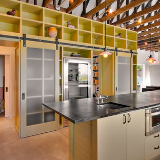 Design ideas for an industrial open plan kitchen in Seattle with flat-panel cabinets, beige cabinets and stainless steel appliances.