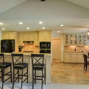Zweizeilige, Mittelgroße Moderne Wohnküche mit Doppelwaschbecken, profilierten Schrankfronten, hellen Holzschränken, Granit-Arbeitsplatte, Küchenrückwand in Beige, Rückwand aus Steinfliesen, schwarzen Elektrogeräten, Terrazzo-Boden und Halbinsel in Dallas