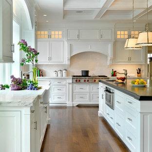 Aménagement d'une cuisine classique avec un évier de ferme, un plan de travail en marbre, des portes de placard blanches, un placard à porte affleurante, une crédence blanche et une crédence en carrelage métro.