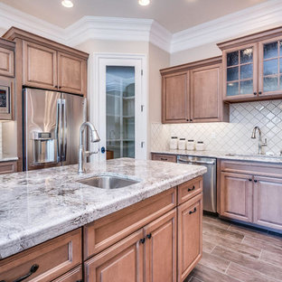 Mid-sized traditional eat-in kitchen inspiration - Example of a mid-sized classic l-shaped dark wood floor and brown floor eat-in kitchen design in Orange County with an undermount sink, raised-panel cabinets, medium tone wood cabinets, granite countertops, white backsplash, ceramic backsplash, stainless steel appliances and an island