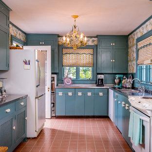 Geschlossene Eklektische Küche ohne Insel in U-Form mit integriertem Waschbecken, Schrankfronten im Shaker-Stil, blauen Schränken, Edelstahl-Arbeitsplatte, Küchenrückwand in Blau, Rückwand aus Keramikfliesen, weißen Elektrogeräten und Terrakottaboden in Sonstige
