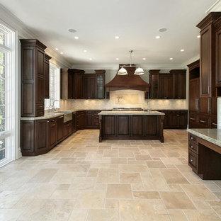 Inredning av ett klassiskt avskilt, stort u-kök, med en rustik diskho, luckor med upphöjd panel, skåp i mörkt trä, granitbänkskiva, beige stänkskydd, stänkskydd i keramik, rostfria vitvaror, klinkergolv i keramik, en köksö och beiget golv