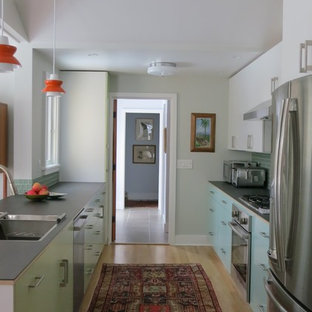 This is an example of a mid-sized midcentury galley kitchen in New York with a single-bowl sink, flat-panel cabinets, glass benchtops and stainless steel appliances.