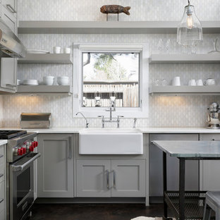 Inspiration for a transitional l-shaped kitchen in Denver with a farmhouse sink, open cabinets, grey cabinets, grey splashback, stainless steel appliances, with island and brown floor.