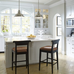 Mid-sized transitional eat-in kitchen ideas - Inspiration for a mid-sized transitional u-shaped limestone floor eat-in kitchen remodel in Bridgeport with an undermount sink, shaker cabinets, white cabinets, quartzite countertops, paneled appliances and an island