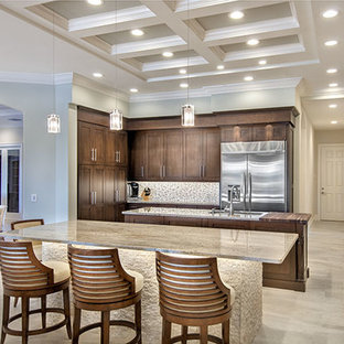 Example of a transitional l-shaped eat-in kitchen design in Tampa with a drop-in sink, shaker cabinets, medium tone wood cabinets, stainless steel appliances and two islands