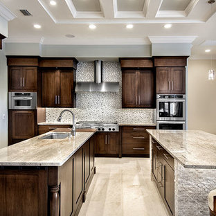 Transitional l-shaped eat-in kitchen photo in Tampa with a drop-in sink, shaker cabinets, medium tone wood cabinets, stainless steel appliances and two islands