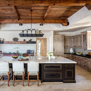 Huge mediterranean kitchen appliance - Huge tuscan l-shaped travertine floor and beige floor kitchen photo in Los Angeles with a farmhouse sink, quartzite countertops, multicolored backsplash, ceramic backsplash, an island, raised-panel cabinets, medium tone wood cabinets and black countertops