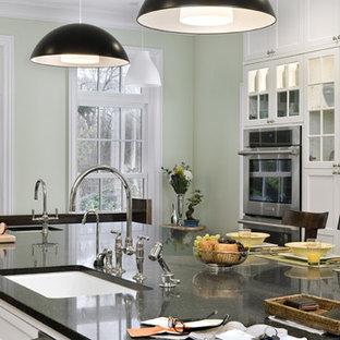 シカゴの広いコンテンポラリースタイルのおしゃれなキッチン (アンダーカウンターシンク、シェーカースタイル扉のキャビネット、白いキャビネット、御影石カウンター、シルバーの調理設備、無垢フローリング、緑の床) の写真