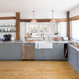 Inspiration for a rural l-shaped kitchen in Boston with a belfast sink, grey cabinets, marble worktops, white splashback, metro tiled splashback, stainless steel appliances, plywood flooring, shaker cabinets and beige floors.