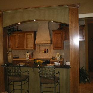 ダラスの中サイズのラスティックスタイルのおしゃれなキッチン (アンダーカウンターシンク、シェーカースタイル扉のキャビネット、中間色木目調キャビネット、御影石カウンター、茶色いキッチンパネル、石タイルのキッチンパネル、シルバーの調理設備の、トラバーチンの床、茶色い床、茶色いキッチンカウンター) の写真