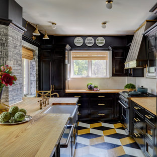 Inspiration for a traditional l-shaped kitchen in Chicago with a farmhouse sink, shaker cabinets, black cabinets, wood benchtops, white splashback, subway tile splashback, stainless steel appliances, painted wood floors, no island, multi-coloured floor and brown benchtop.
