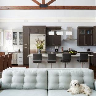 Idéer för ett klassiskt kök, med en undermonterad diskho, skåp i shakerstil, bruna skåp, rostfria vitvaror, mörkt trägolv och en köksö