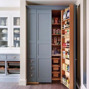 Modelo de cocina tradicional con despensa, armarios estilo shaker, puertas de armario grises y suelo de madera en tonos medios