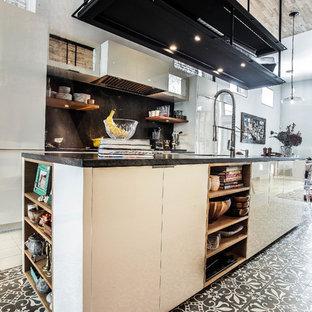 シカゴの大きいエクレクティックスタイルのおしゃれなキッチン (アンダーカウンターシンク、フラットパネル扉のキャビネット、白いキャビネット、ガラスカウンター、白いキッチンパネル、シルバーの調理設備の、マルチカラーの床) の写真