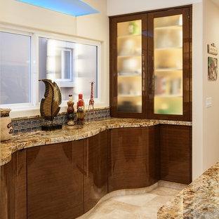 オレンジカウンティの広いエクレクティックスタイルのおしゃれなキッチン (アンダーカウンターシンク、フラットパネル扉のキャビネット、中間色木目調キャビネット、御影石カウンター、マルチカラーのキッチンパネル、石スラブのキッチンパネル、シルバーの調理設備、ライムストーンの床) の写真