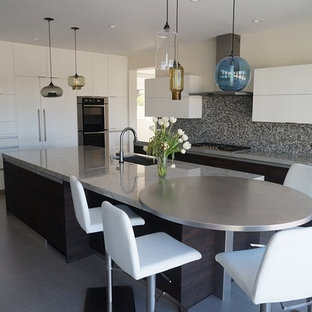 Design ideas for a large eclectic l-shaped open plan kitchen in Orange County with a double-bowl sink, flat-panel cabinets, white cabinets, glass benchtops, black splashback, glass tile splashback, stainless steel appliances, porcelain floors and with island.