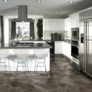 Immagine di una grande cucina design con ante lisce, ante bianche, top in granito, paraspruzzi bianco, elettrodomestici in acciaio inossidabile, pavimento in linoleum e penisola