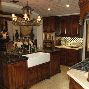 ロサンゼルスの中サイズのヴィクトリアン調のおしゃれなキッチン (エプロンフロントシンク、レイズドパネル扉のキャビネット、濃色木目調キャビネット、タイルカウンター、マルチカラーのキッチンパネル、モザイクタイルのキッチンパネル、シルバーの調理設備の、トラバーチンの床) の写真