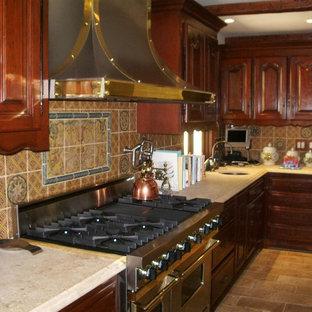 Inredning av ett medelhavsstil mellanstort kök, med luckor med upphöjd panel, skåp i mellenmörkt trä, bänkskiva i kalksten, stänkskydd i keramik, rostfria vitvaror, tegelgolv och en köksö