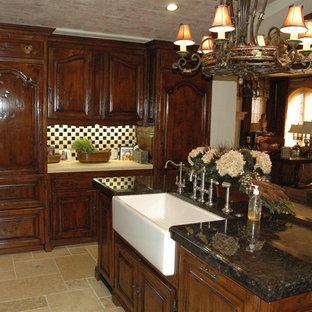 ロサンゼルスの中サイズの地中海スタイルのおしゃれなキッチン (エプロンフロントシンク、レイズドパネル扉のキャビネット、濃色木目調キャビネット、タイルカウンター、マルチカラーのキッチンパネル、モザイクタイルのキッチンパネル、シルバーの調理設備の、トラバーチンの床) の写真