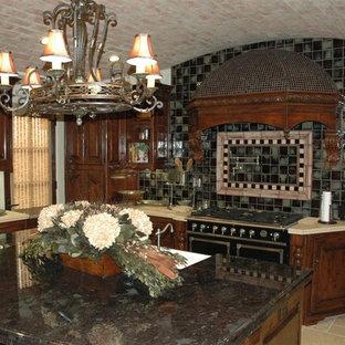 ロサンゼルスの中サイズの地中海スタイルのおしゃれなキッチン (エプロンフロントシンク、レイズドパネル扉のキャビネット、濃色木目調キャビネット、タイルカウンター、マルチカラーのキッチンパネル、モザイクタイルのキッチンパネル、黒い調理設備、トラバーチンの床) の写真
