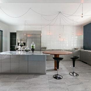 Cette image montre une cuisine américaine design en L avec un évier encastré, un placard à porte plane, des portes de placard grises, un électroménager encastrable et un îlot central.