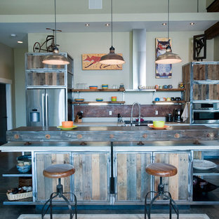 This is an example of a large industrial galley open plan kitchen in Other with an integrated sink, distressed cabinets, concrete benchtops, brown splashback, metal splashback, stainless steel appliances, concrete floors and with island.