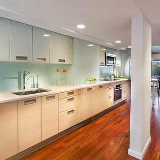 Example of a large trendy single-wall medium tone wood floor and brown floor eat-in kitchen design in New York with flat-panel cabinets, a single-bowl sink, stainless steel appliances, blue backsplash, light wood cabinets, glass tile backsplash and no island