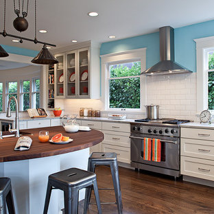Photo of a mid-sized contemporary u-shaped eat-in kitchen in Seattle with shaker cabinets, white cabinets, wood benchtops, white splashback, subway tile splashback, stainless steel appliances, a farmhouse sink, dark hardwood floors, a peninsula and brown floor.