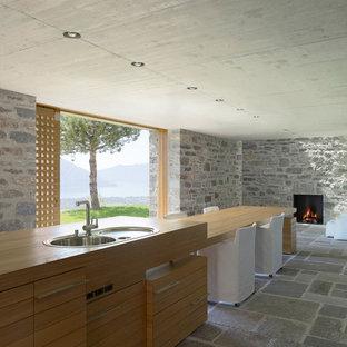 На фото: огромная параллельная кухня в современном стиле с обеденным столом, монолитной раковиной, плоскими фасадами, фасадами цвета дерева среднего тона, деревянной столешницей, бежевым фартуком, фартуком из каменной плитки, техникой из нержавеющей стали, полом из известняка и двумя и более островами