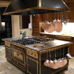 Large mediterranean u-shaped kitchen pantry in New York with an integrated sink, shaker cabinets, dark wood cabinets, soapstone benchtops, multi-coloured splashback, stone tile splashback, coloured appliances, limestone floors and with island.