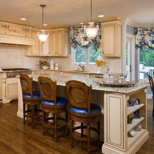ニューヨークの広いヴィクトリアン調のおしゃれなキッチン (ドロップインシンク、レイズドパネル扉のキャビネット、ベージュのキャビネット、御影石カウンター、ベージュキッチンパネル、シルバーの調理設備、濃色無垢フローリング、セラミックタイルのキッチンパネル、茶色い床、グレーのキッチンカウンター) の写真