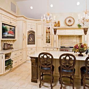 Exemple d'une grand cuisine américaine victorienne en U avec un placard avec porte à panneau surélevé, des portes de placard beiges, un plan de travail en granite, une crédence beige, une crédence en carrelage de pierre, un électroménager en acier inoxydable, un sol en travertin, un îlot central, un évier encastré et un sol beige.