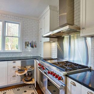 ニューヨークのおしゃれなキッチン (エプロンフロントシンク、シェーカースタイル扉のキャビネット、白いキャビネット、白いキッチンパネル、サブウェイタイルのキッチンパネル、シルバーの調理設備、大理石カウンター) の写真