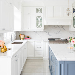 Photo of a mid-sized transitional l-shaped open plan kitchen in San Diego with a double-bowl sink, shaker cabinets, white cabinets, white splashback, stone slab splashback, stainless steel appliances, marble floors, with island, marble benchtops and white floor.