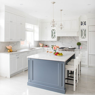 Mid-sized transitional l-shaped open plan kitchen in Toronto with a double-bowl sink, white cabinets, white splashback, stone slab splashback, stainless steel appliances, with island, shaker cabinets, marble floors, white floor, quartz benchtops and white benchtop.