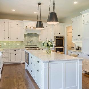 Klassisk inredning av ett stort kök, med en rustik diskho, luckor med glaspanel, vita skåp, bänkskiva i terrazo, grönt stänkskydd, stänkskydd i glaskakel, mellanmörkt trägolv, en köksö och rostfria vitvaror