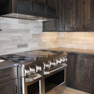 Ejemplo de cocina rural con armarios estilo shaker, puertas de armario de madera en tonos medios, encimera de zinc, salpicadero verde, salpicadero de azulejos de porcelana, electrodomésticos de acero inoxidable y suelo de madera clara