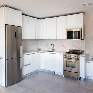 Foto de cocina en L, minimalista, grande, sin isla, con armarios tipo vitrina, puertas de armario blancas, encimera de vidrio, salpicadero blanco y encimeras amarillas
