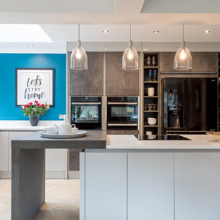 Photo of a medium sized contemporary u-shaped kitchen in Sussex with a submerged sink, flat-panel cabinets, white cabinets, an island, beige floors and white worktops.