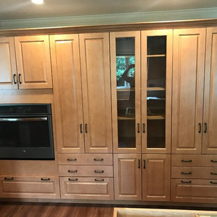 This is an example of a traditional kitchen in Other with raised-panel cabinets, orange cabinets, quartzite benchtops, vinyl floors, with island and brown floor.