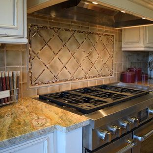 Inspiration for a timeless travertine floor kitchen remodel in Other with distressed cabinets, granite countertops, brown backsplash, ceramic backsplash and stainless steel appliances